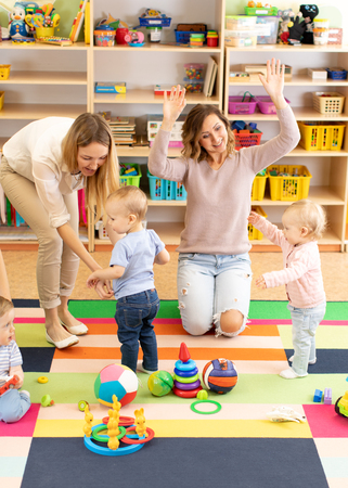 Group of kids toddlers playing with colorful educational toys together with mothers in children nursery playroom Stok Fotoğraf