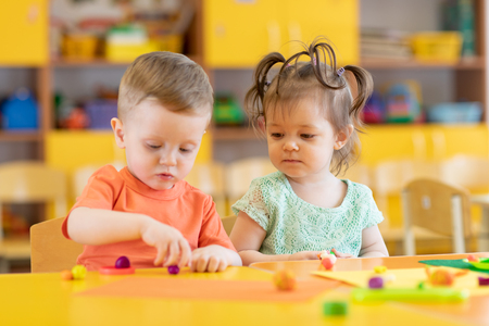 little kids friends girl and boy molding of plasticine in nursery