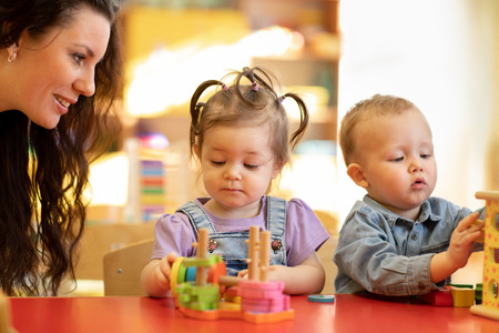 Teacher teaching kids play toy in classroom. Kindergarten pre school concept Stok Fotoğraf