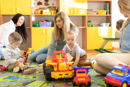 Young women communicate while their kids playing with toys in daycare Stok Fotoğraf