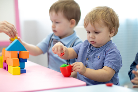 Kinder Kleinkinder spielen buntes Tonspielzeug im Kindergarten Standard-Bild