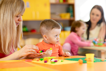 Kindergarten kids with teacher mould from plasticine on table in nursery Stok Fotoğraf