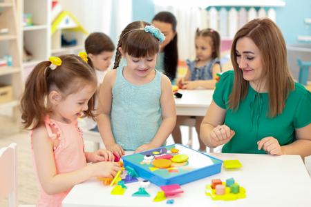Niños niños jugando con constructor en la mesa en el jardín de infantes