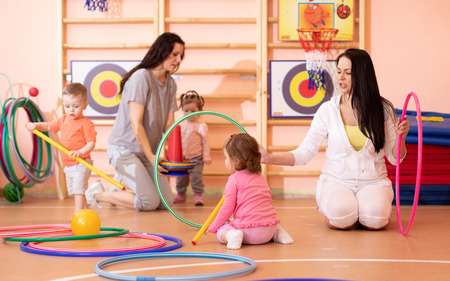 Kids toddlers play with hoops in kindergarten gym