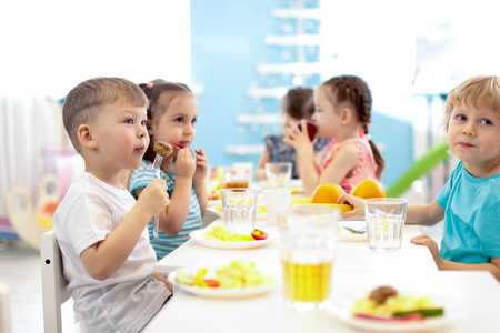 Kids have a lunch in daycare centre. Children eating healthy food in kindergarten Stok Fotoğraf