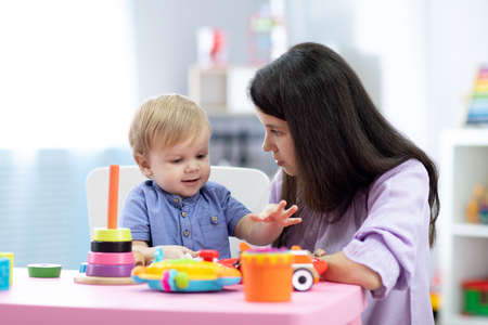 Baby boy plays with mother or teacher in nursery or day care centre