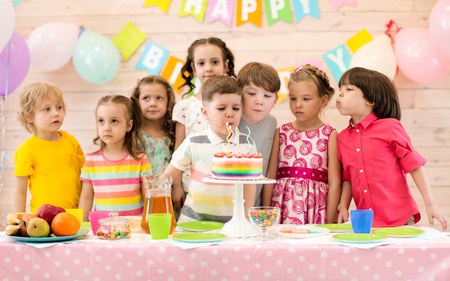 Group of children blowing candles on cake at birthday party