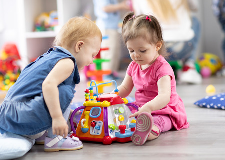 children girls play together educational toys in playroom