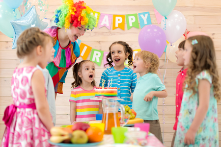 Group of children with clown blowing candles on cake at birthday party