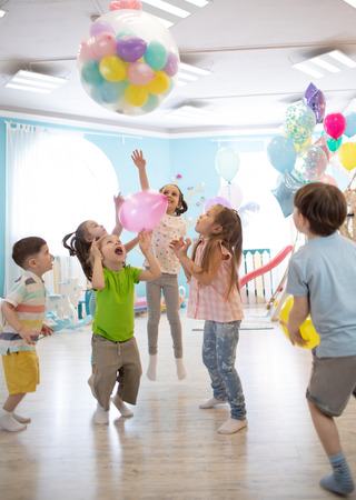 holidays, childhood and celebration concept - several kids having fun and jumping on birthday party in entertainment centre Stok Fotoğraf