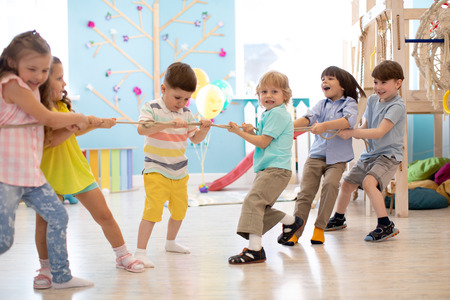 group of kids play and pull rope together in daycare Stok Fotoğraf
