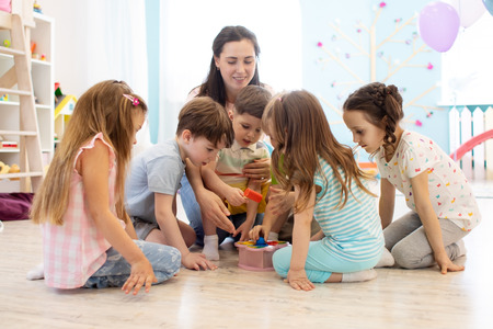 Preschool teacher plays with group of kids sitting on a floor at kindergarten Stok Fotoğraf
