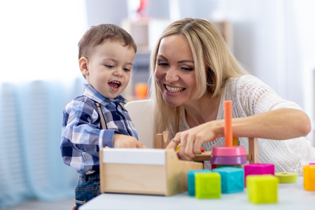 Cute kid and mother playing with toys at home. Little boy having fun pastime in nursery.