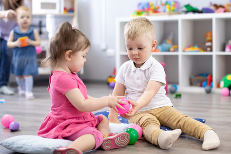 Little toddlers boy and a girl playing together in nursery room. Preschool children in day care centre Banco de Imagens