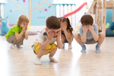 Group of kids squatting on floor in daycare, having fun and playing hide and seek game, hiding the face with hands. Happy childhood concept. Stok Fotoğraf