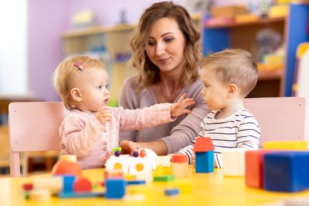 Bebés en el jardín de infancia. Niños pequeños en la escuela de párvulos. Niños en edad preescolar de niña y niño jugando con el maestro. Foto de archivo