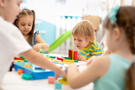 Grupo de niños de jardín de infantes en la guardería. Niños felices jugando con bloques de plástico en el jardín de infantes