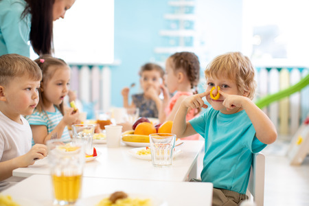 Group of kids have lunch in daycare