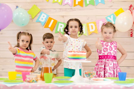 Children celebrating birthday party. Happy kids show thumbs up Stok Fotoğraf