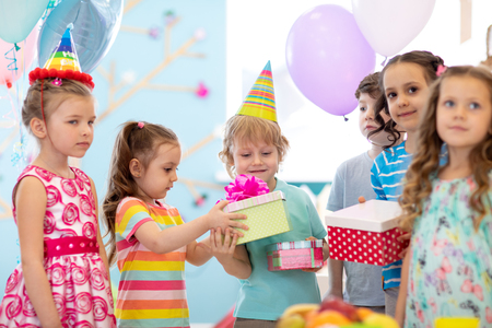 Childhood, holidays, celebration and friendship concept. Happy children in party hats giving gifts at birthday party Stok Fotoğraf