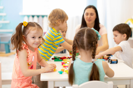 Cute woman and kids playing educational toys at kindergarten or nursery room