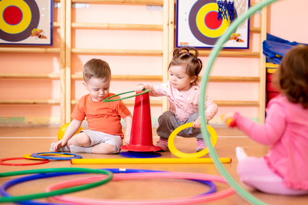 Nursery babies group play with rings in gym Stok Fotoğraf