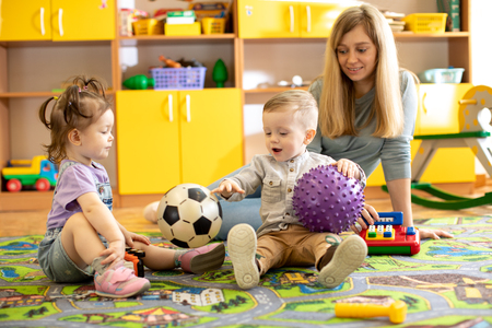 Nursery teacher looking after children in kindergarten. Little kids toddlers play together with toys.