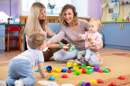 Nursery kids playing with toys. Mothers communicate and look after their children