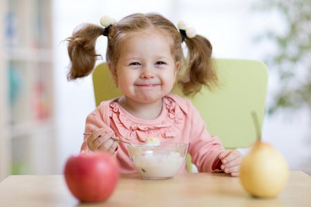 Fille enfant mangeant avec une cuillère