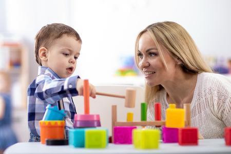 Guardería bebé y cuidador jugar con juguetes montessori en la mesa en la guardería Foto de archivo