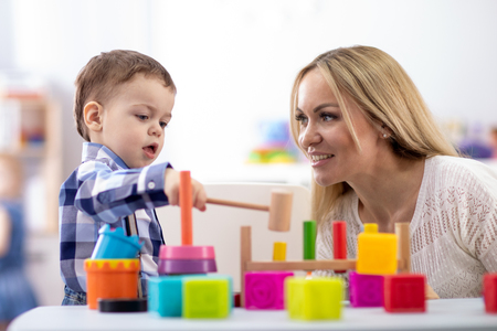 Nursery baby and caregiver play with montessori toys at table in daycare centre Stok Fotoğraf