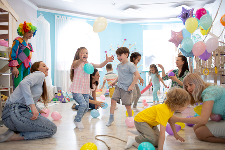joyful kids and their parents entertain and have fun with color balloon on birthday party Stok Fotoğraf