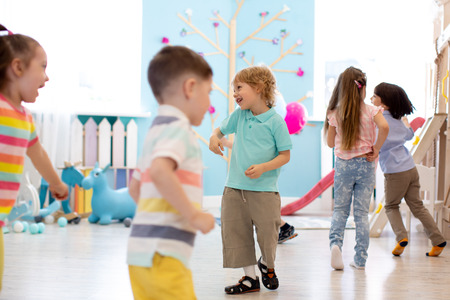 childhood, leisure and people concept - group of happy kids playing tag game and running in spacious room Stok Fotoğraf