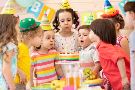Kinder, die Geburtstagsfeier feiern und Kerzen auf Kuchen blasen