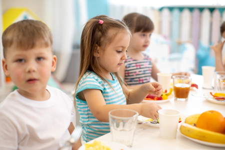 Group of children eating healthy food in daycare centre Stok Fotoğraf
