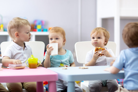 Group of children eating food in daycare centre