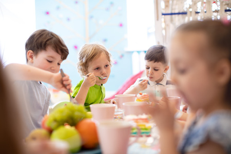 Children eat cake at birthday party