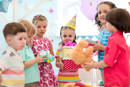 Childhood, holidays, celebration and friendship concept. Happy kids giving gifts at birthday party Stok Fotoğraf