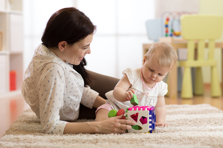 Mother and baby girl playing with developmental toys in nursery room Stok Fotoğraf