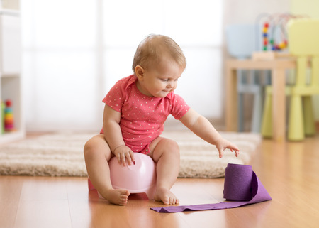 Happy one year old baby girl sitting on chamber pot