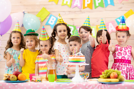 Group of children having fun celebrating birthday party. Kids showing thumbs up sign Stok Fotoğraf