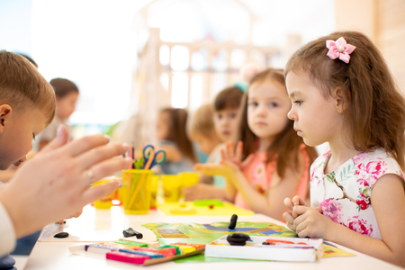 kids group learning arts and crafts in daycare centre