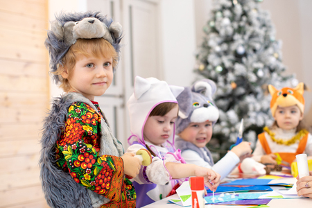 Children handiwork in kids club. Craft lesson in primary school. Kid boy together friends weared animal costumes in class. Group of kindergarten childs work preparing to christmas