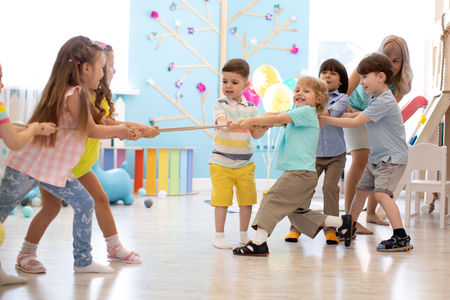 group of kids play and pull rope together in daycare Banco de Imagens