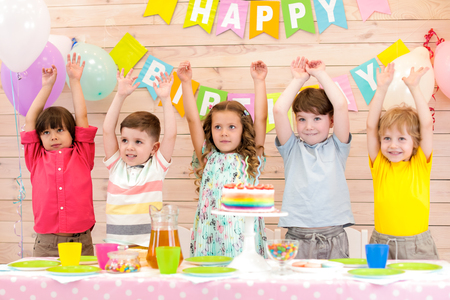 Group of five children smiling standing in a row beside birthday table with cake on it holding hands up