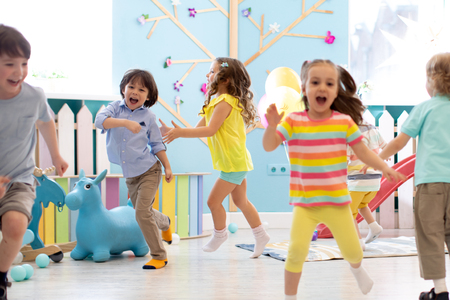 Group of happy children of boys and girls run in day care. Kids play in kindergarten