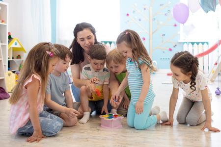 Female teacher teaching kids play toy in class room. Kindergarten preschool concept