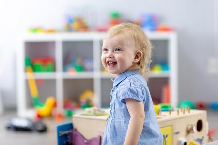 Portrait of pretty baby girl in kindergarten. Nursery child is happy