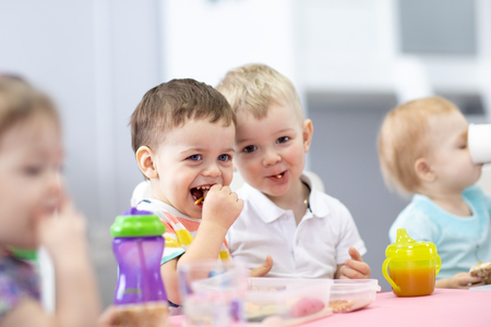 Group of kids have a lunch in kindergarten