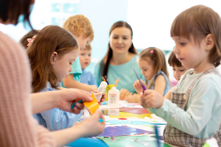 Development learning children in preschool. Childrens project in kindergarten. Group of kids and teacher cutting paper and gluing with glue stick on art class in kindergarten or daycare centre Banco de Imagens